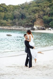 Belle coppie nell'amore che abbraccia sulla spiaggia sull'oceano.