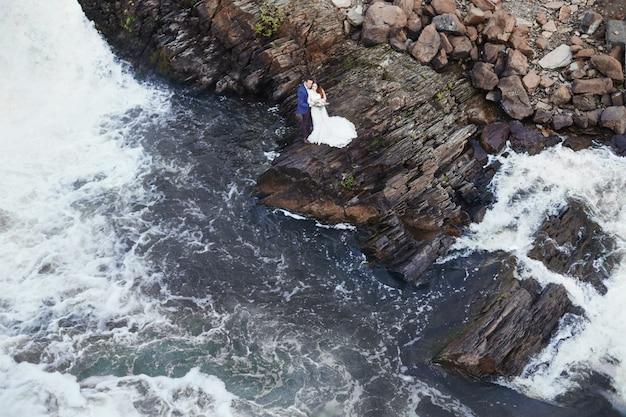 Belle coppie nell'amore che bacia mentre sedendosi sulle rocce vicino al mare. sposi