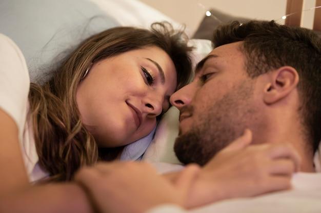 Belle coppie sveglie che abbracciano a casa