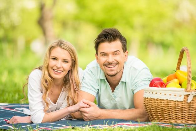 Belle coppie vestite casual sdraiato sul prato nel parco.