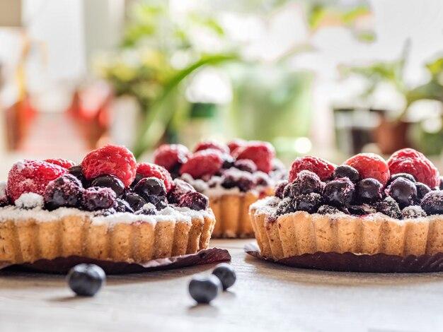 Belle deliziose crostate, dolci colorati torte di pasticceria con lamponi freschi e mirtilli su fondo di legno bianco.