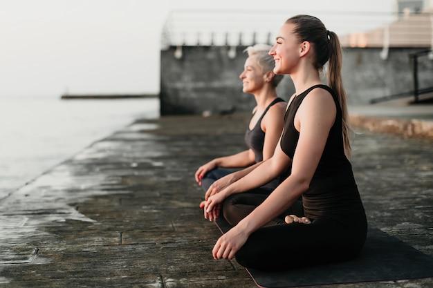 Belle donne adatte sorridenti che meditano vicino all'acqua che si siede sulla stuoia di yoga