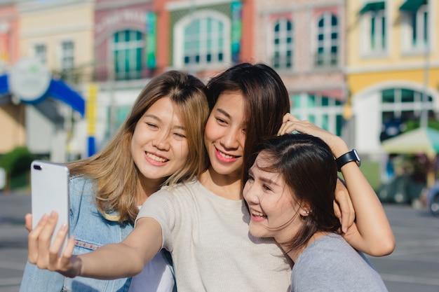 Belle donne asiatiche attraenti degli amici che per mezzo di uno smartphone. felice giovane adolescente asiatico in città urbana