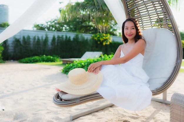 Belle donne asiatiche del ritratto intorno all'oceano del mare della spiaggia con il sorriso felice
