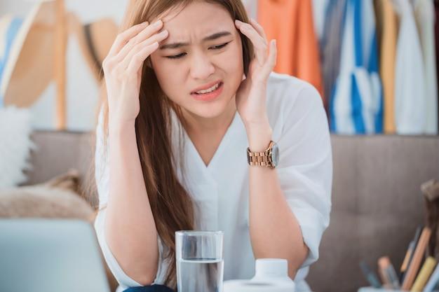 Belle donne asiatiche stressanti e mal di testa dopo aver lavorato con un computer portatile