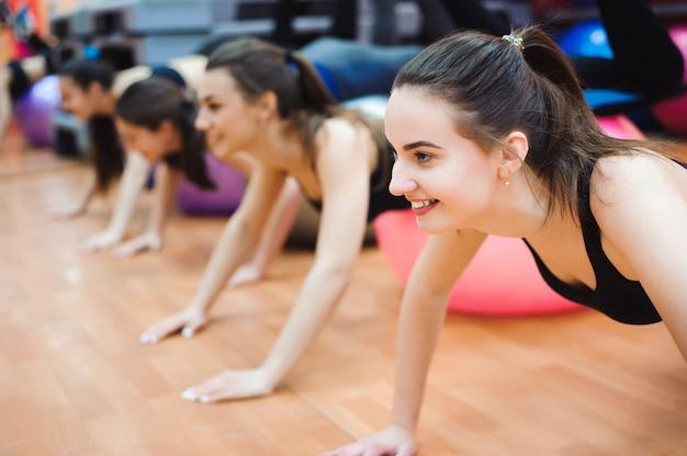 Belle donne caucasiche che fanno esercizio con la palla relativa alla ginnastica.