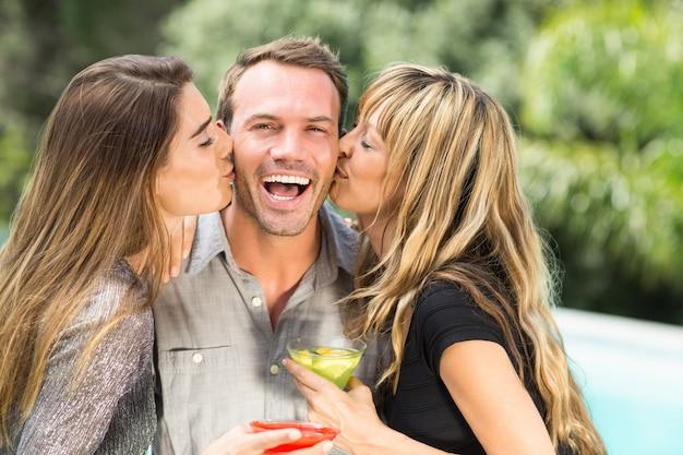 Belle donne che baciano uomo felice