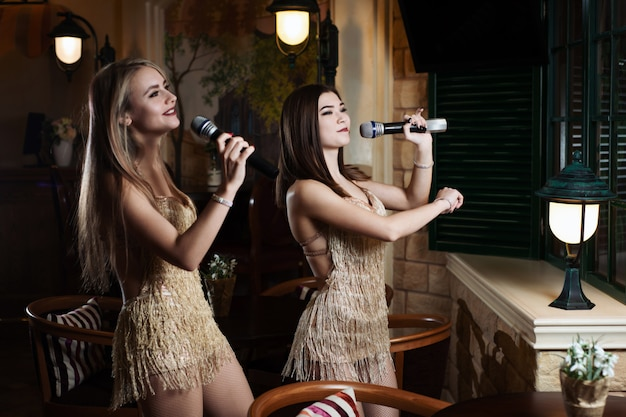 Belle donne che cantano le canzoni di karaoke nei microfoni nel ristorante