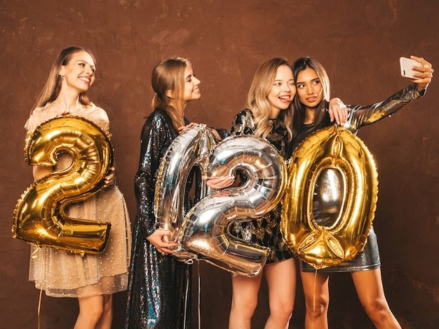 Belle donne che celebrano il nuovo anno belle ragazze felici in eleganti abiti da festa sexy con palloncini d'oro e d'argento 2020, divertendosi alla festa di san silvestro. facendo selfie o video per instagram