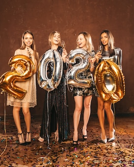 Belle donne che celebrano il nuovo anno belle ragazze felici in eleganti abiti da festa sexy