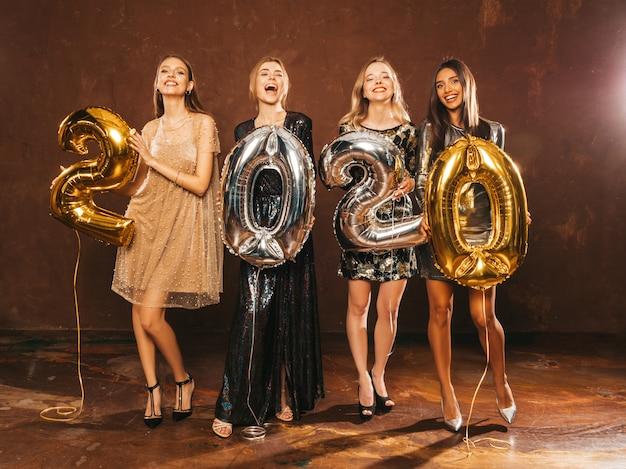 Belle donne che celebrano il nuovo anno. ragazze bellissime felici in eleganti abiti da festa sexy con palloncini oro e argento 2020, divertendosi alla festa di capodanno. celebrazione festiva. modelli affascinanti