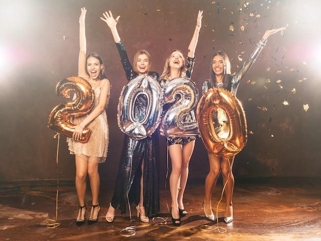 Belle donne che celebrano il nuovo anno. ragazze bellissime felici in eleganti abiti da festa sexy con palloncini oro e argento 2020, divertendosi alla festa di capodanno. festeggiamenti festivi. mani alzanti