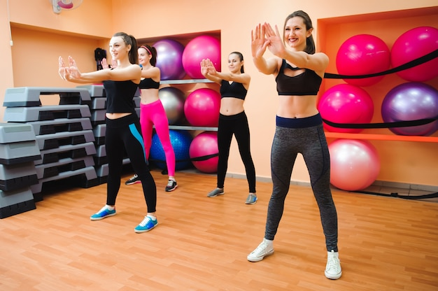 Belle donne che esercitano aerobica nel fitness club.