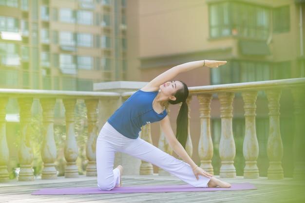 Belle donne che praticano yoga sul balcone al mattino.