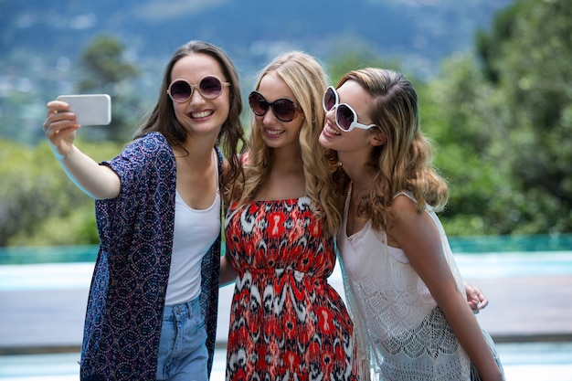 Belle donne che prendono un selfie dalla piscina