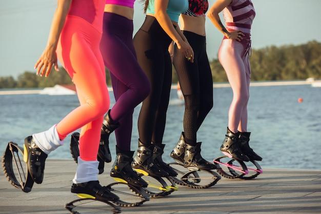 Belle donne in abbigliamento sportivo con scarpe da salto kangoo