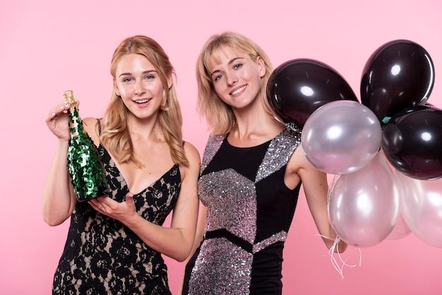 Belle donne in possesso di palloncini e champagne