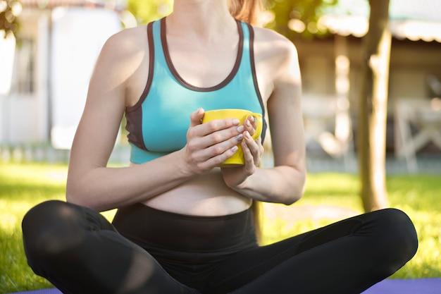 Belle donne incinte che si siedono sulla stuoia di yoga con la tazza di tè. mattina d'estate in giardino.