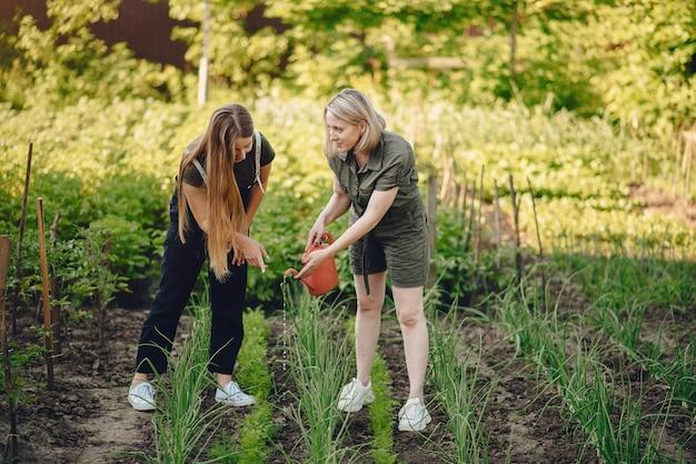 Belle donne lavora in un giardino vicino alla casa
