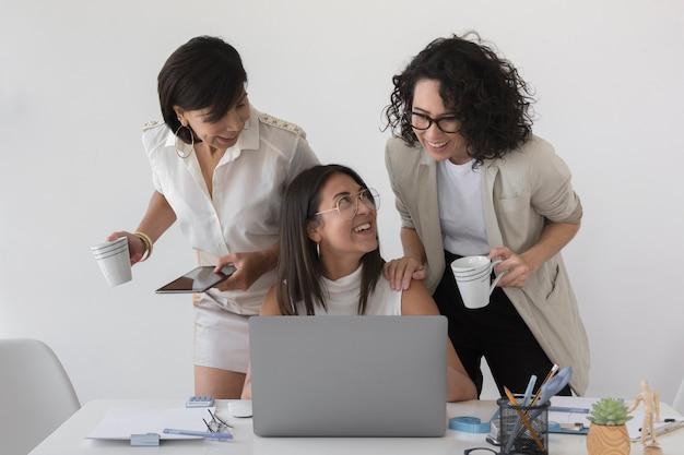 Belle donne moderne di vista frontale che lavorano insieme