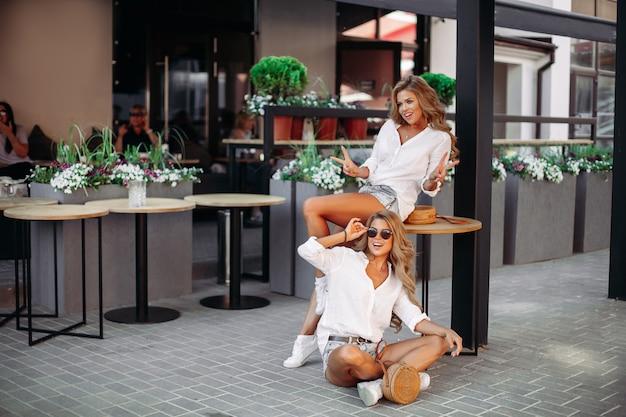 Belle donne, mostrando la pace, in posa all'aperto nella caffetteria