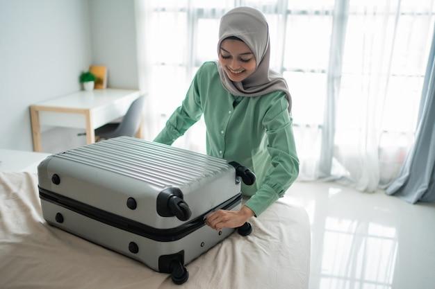 Belle donne musulmane che cercano di chiudere la sua valigia piena
