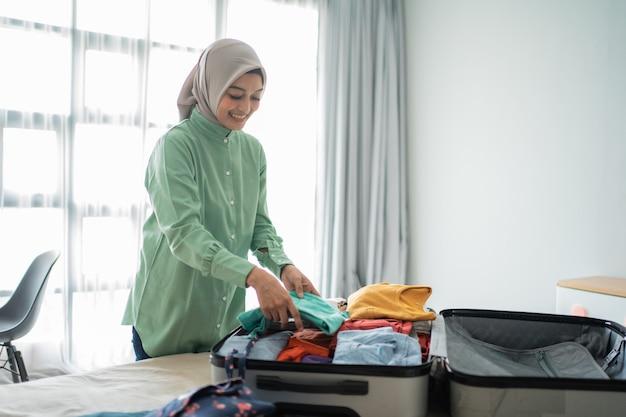 Belle donne musulmane che preparano valigia