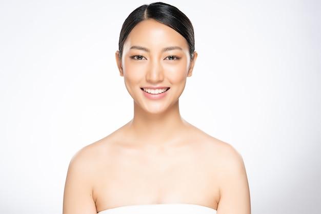 Belle donne sorridenti con pelle pulita, trucco naturale e denti bianchi su sfondo bianco.