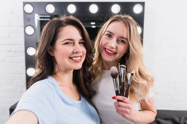 Belle donne sorridenti con spazzole prendendo selfie