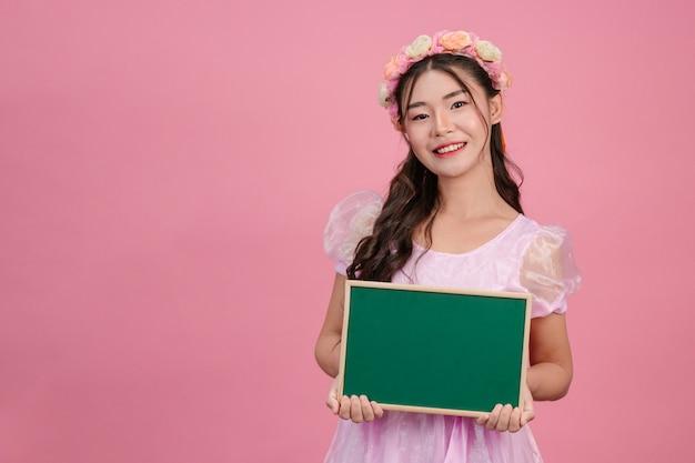 Belle donne vestite in abiti da principessa rosa tengono un bordo verde su una rosa.