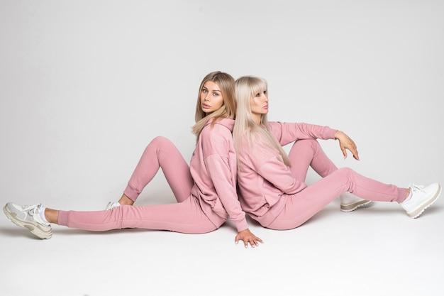 Belle due signore sedute schiena contro schiena e che mostrano costumi autunnali caldi mentre posano su sfondo grigio