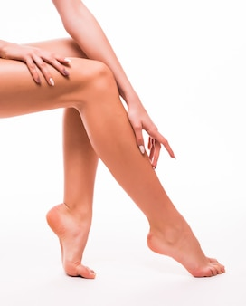 Belle gambe della donna con pelle bianca liscia isolata su bianco