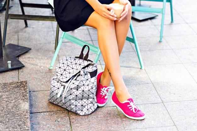 Belle gambe della donna, ragazza seduta in un caffè all'aperto, che tiene una tazza di cappuccino, caffè, in ritardo nelle mani. indossare scarpe di gomma rosa, elegante zaino argento accanto alle scarpe.