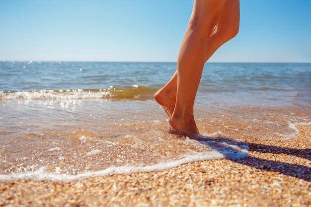 Belle gambe di una bella ragazza che cammina in acqua