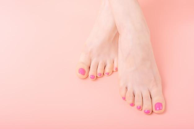 Belle gambe femminili ben curate del primo piano con il pedicure luminoso su un fondo rosa, spazio della copia, concetto dello skincare