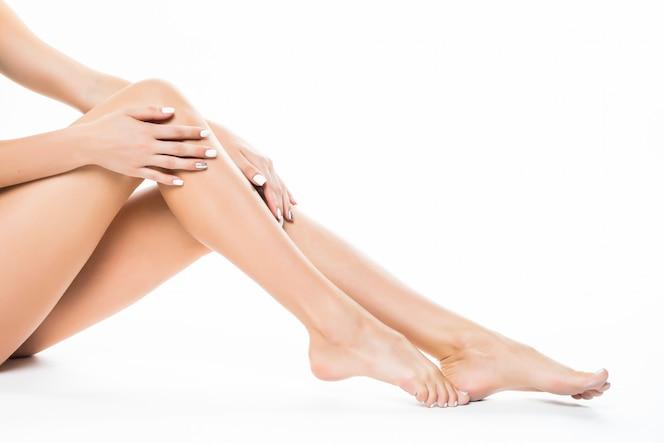 Belle gambe femminili, corpo posteriore dell'asino isolato sopra la parete bianca che si trova sul pavimento con il concetto di cura della pelle lunga gamba, spa e bellezza.