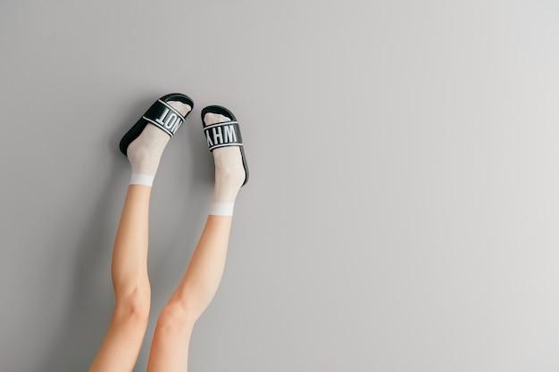 Belle gambe femminili in calze bianche e pantofole alla moda