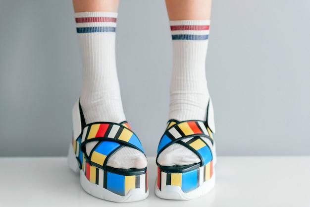 Belle gambe femminili in calze bianche e scarpe colorate