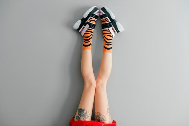 Belle gambe femminili in calzini colorati e scarpe alla moda