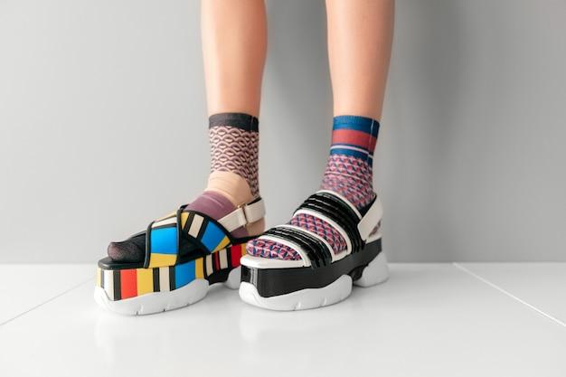 Belle gambe femminili in calzini e sandali colorati non corrispondenti