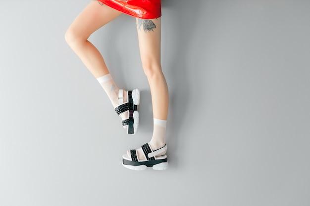 Belle gambe femminili in sandali alla moda e calze bianche