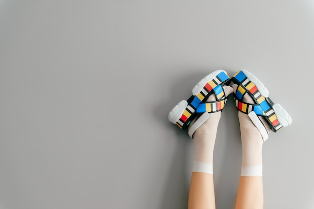 Belle gambe femminili in sandali colorati e calze bianche