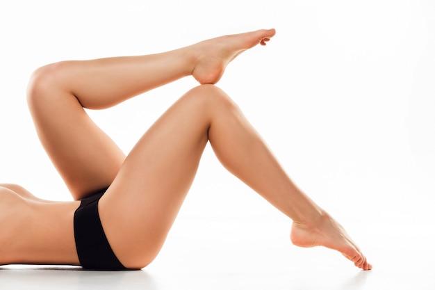 Belle gambe femminili isolate su bianco. concetto di bellezza e fitness