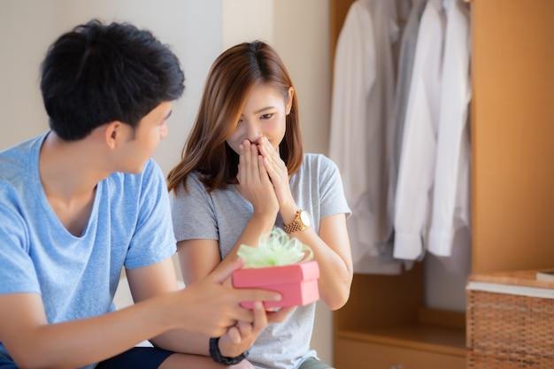 Belle giovani coppie asiatiche nell'amore con il contenitore di regalo di sorpresa