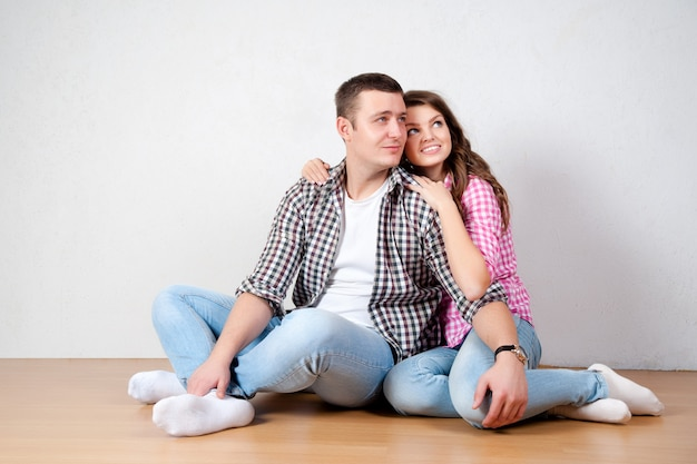 Belle giovani coppie barefoot in jeans casuali che si siedono pendente contro una parete bianca sul pavimento di legno nel salone che sorride alla macchina fotografica