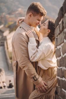 Belle giovani coppie che abbracciano alla grande muraglia cinese