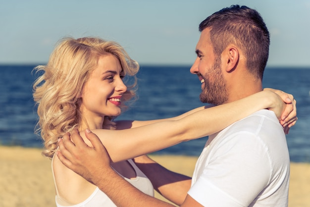 Belle giovani coppie che abbracciano, guardando a vicenda.
