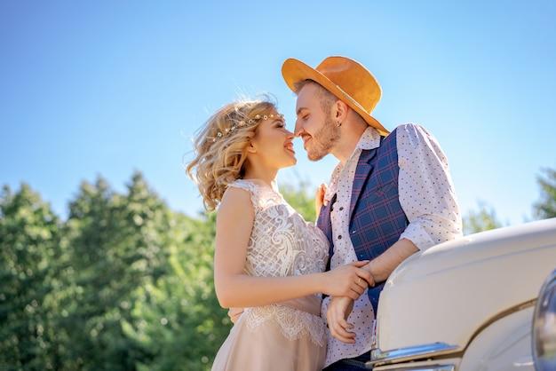 Belle giovani coppie che abbracciano vicino all'automobile