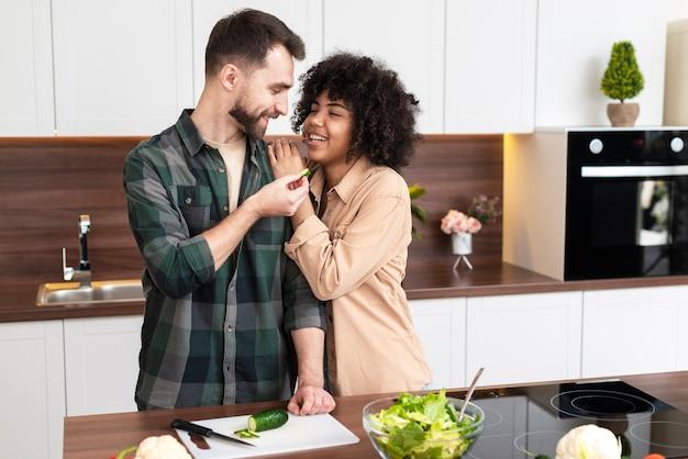 Belle giovani coppie che cucinano insieme