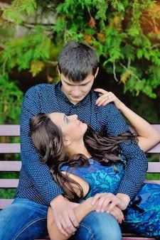 Belle giovani coppie che hanno picnic in campagna. famiglia felice all'aperto. rilassamento sorridente della donna e dell'uomo